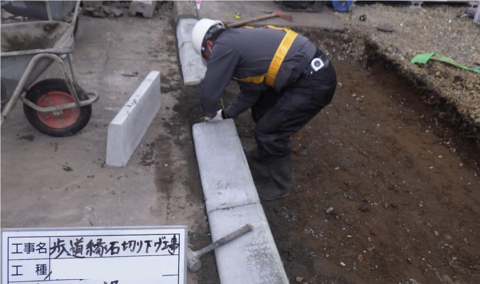 歩道切り下げ工事。切り下げ用の縁石を敷設している様子