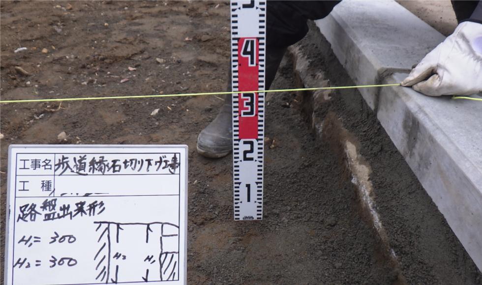 歩道切り下げ工事。路床までの深さを計測している写真
