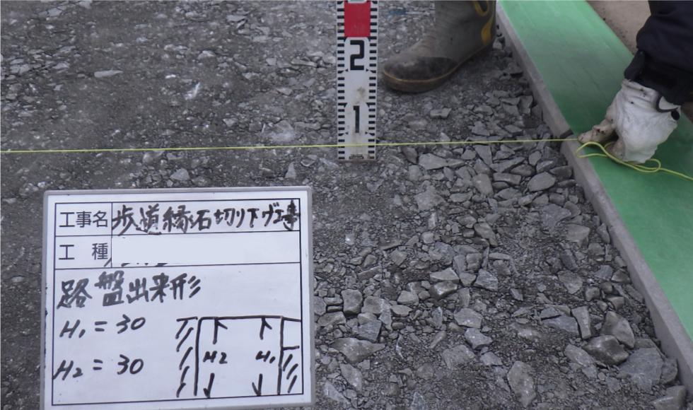 歩道切り下げ工事。路盤の深さを計測している写真