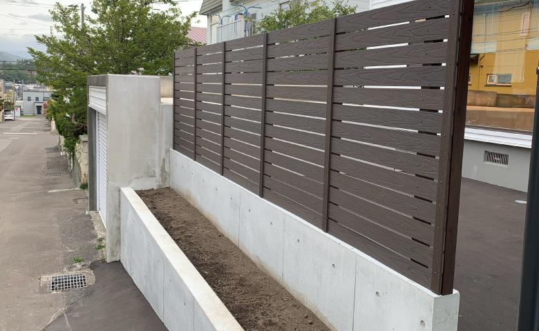 コンクリート基礎とフェンスを撮影した写真