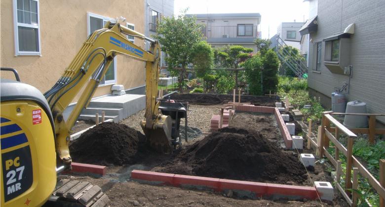 ユンボで庭を掘削している様子