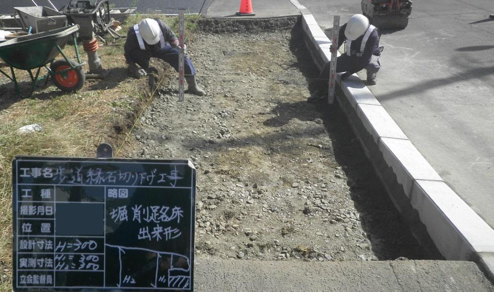 縁石敷設後、路床の高さを計測した写真